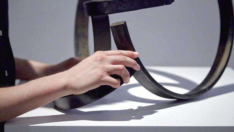 Persona ciega explorando una escultura de Jorge Oteiza